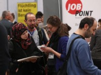 BERLIN, GERMANY - JANUARY 25:  A young woman from Syria (L) learns about job opportunities at the second annual jobs fair for refugees and migrants at the Estrel hotel and conference venue on January 25, 2017 in Berlin, Germany. The intiative brings together exhibitors from retail, the service industry, manufacturing, employment agencies and other branches who are recruiting people from among the hundreds of thousands of migrants and refugees who arrived in Germany in recent years. Germany is taking active measures across both the public and private spheres to encourage the integration and employment of the newcomers.  (Photo by Sean Gallup/Getty Images)