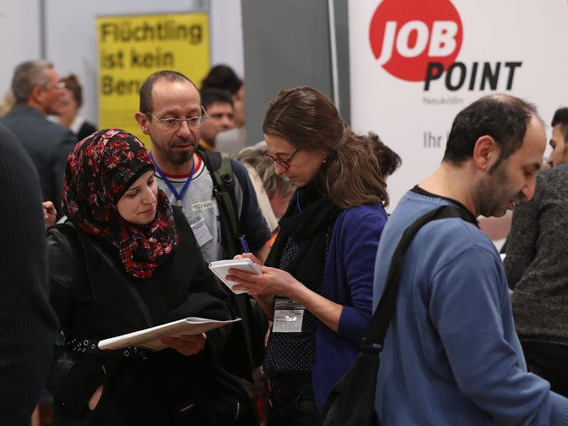 BERLIN, GERMANY - JANUARY 25: A young woman from Syria (L) learns about job opportunities at the second annual jobs fair for refugees and migrants at the Estrel hotel and conference venue on January 25, 2017 in Berlin, Germany. The intiative brings together exhibitors from retail, the service industry, manufacturing, …