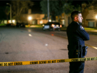 A police officer stands guard inside an area roped off with crime scene tape near a home being investigated by police on Thursday, Dec. 3, 2015, in Redlands, Calif. A heavily armed man and woman opened fire Wednesday on a holiday banquet for his co-workers, killing multiple people and seriously wounding others in a precision assault, authorities said. Hours later, they died in a shootout with police. (AP Photo/Ringo H.W. Chiu)