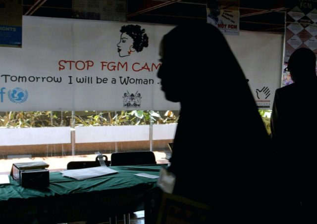 A young woman walks past a banner against female genital mutilation