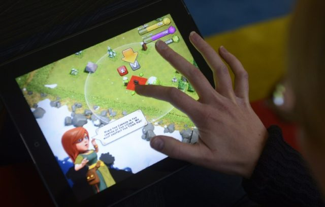 A woman plays 'Clash of Clans' on a tablet computer in Helsinki