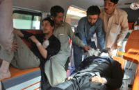Volunteers transport blast victims to a hospital in Peshawar on February 21, 2017, after the suicide bombings at a court in Tangi