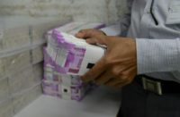 An Indian bank employee checks stacks of new 2,000 rupee notes