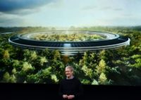 Apple CEO Tim Cook stands in front of a slide of the company's new campus which is under construction in 2016