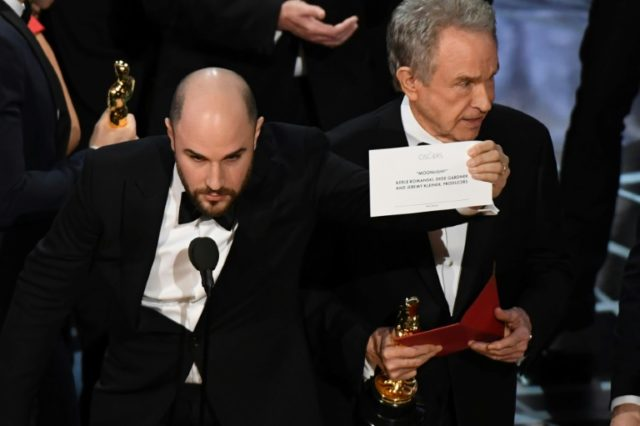 """La La Land"" producer Jordan Horowitz (L) holds up the card reading Best Film 'Moonlight"" next to US actor Warren Beatty after the latter mistakingly read ""La La Land"" initially at the 89th Oscars in Hollywood, California on February 26, 2017"