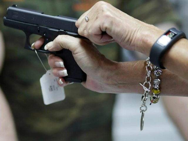 Sally Abrahamsen, of Pompano Beach, Fla., right, holds a Glock 42 pistol while shopping for a gun at the National Armory gun store and gun range, Tuesday, Jan. 5, 2016, in Pompano Beach, Fla. President Barack Obama unveiled his plan Tuesday to tighten control and enforcement of firearms in the U.S. At left is salesperson T.J. O'Reilly. (AP Photo/Lynne Sladky)