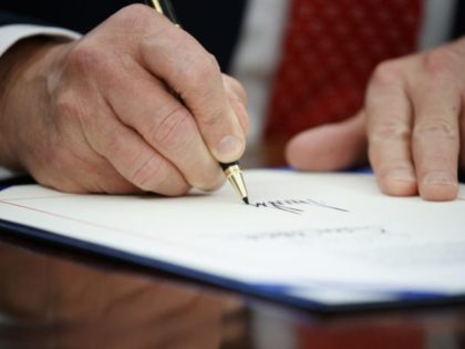 President Donald Trump signs one of two executive orders aimed at supporting women in STEM fields, Tuesday, Feb. 28, 2017, in the Oval Office of the White House in Washington. (AP Photo/Evan Vucci)