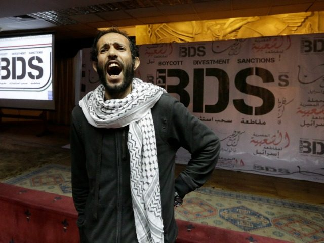 An Egyptian shouts anti-Israeli slogans in front of banners with the Boycott, Divestment and Sanctions (BDS) logo during the launch of the Egyptian campaign that urges boycott, divestment and sanctions against Israel and Israeli-made goods, at the Egyptian Journalists' Syndicate in Cairo, Egypt, Monday, April 20, 2015. BDS is a …