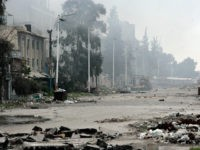 In this photo released by the Syrian official news agency SANA, damaged and blocked street where clashes erupted between the Syrian government forces and rebels, near the Abbassiyin square, east Damascus, Syria, Monday March 20, 2017. Syrian government forces on Monday regained control of parts of Damascus that were attacked and captured by rebels and militants the previous day, with the two-day fighting leaving dozens dead on both sides, the military and an activist group said. (SANA via AP)