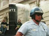 A police officer stands guard as two Greenpeace demonstrators, left, chain themselves to a mock incinerator smokestack atop a bus during a protest October 25, 2000 outside the Environmental Protection Agency in Washington. Activists chained themselves to a bus outside the EPA building Wednesday to protest an Ohio incinerator that …