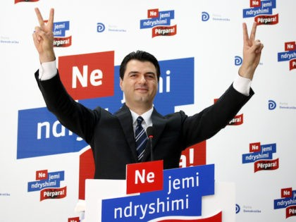 """Lulzim Basha, the newly elected leader of the Democratic Party (DP), soon to be in opposition after the June 23rd general elections, flashes """"V for victory"""" signs during a press conference in Tirana on July 23, 2013. Basha won with 80 percent of the votes an internal race for the …"""