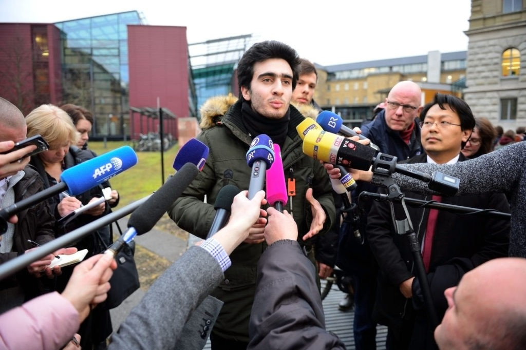 WURZBURG, GERMANY - FEBRUARY 06:  Lawyer Chan-Jo Jun (R) and the Syrian refugee Anas Modamani (C) speaks to the media after the court session over Modamani's lawsuit against Facebook at the Landgericht courthouse on February 6, 2017 in Wurzburg, Germany. Modamani is suing Facebook over selfie photos of himself with German Chancellor Angela Merkel that he says were misused by Facebook users accusing him of being a terrorist or guilty of other crimes and that Facebook refused to remove. This is the first time Facebook is being taken to court in Germany.  (Photo by Thomas Lohnes/Getty Images)