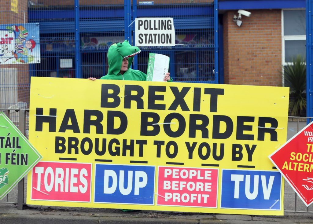 A Sinn Fein party election worker dressed up as a crocodile stands behind a banner referring to Brexit outside a polling station in Belfast on March 2, 2017 as voters in Northern Ireland go to the polls to elect a new Assembly.  Northern Ireland began voting Thursday in snap elections to resolve a political crisis fuelled by bad blood and Brexit, which is testing the delicate peace in the British province. Long-simmering tensions boiled over in January when the Sinn Fein party -- once the political arm of the Irish Republican Army -- brought down the province's semi-autonomous government. / AFP PHOTO / Paul FAITH        (Photo credit should read PAUL FAITH/AFP/Getty Images)
