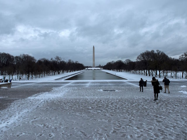 Visitors walk along the National Mall after a winter storm March 14, 2017 in Washington, DC. Winter Storm Stella dumped snow and sleet Tuesday across the northeastern United States where thousands of flights were canceled and schools closed, but appeared less severe than initially forecast. / AFP PHOTO / Brendan …