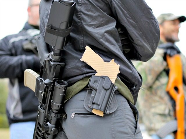 FILE - In this Jan. 13, 2015, file photo, a gun-rights advocate carries a rifle on his back and a cardboard cutout of a pistol on his waist as a group protests outside the Texas Capitol, in Austin, Texas. Texas lawmakers on Friday, May 29, 2015, approved carrying handguns openly …