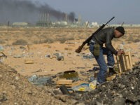 A Libyan rebel volunteer near the wealthy oil town of Ras Lanuf, looking for ammunition amongst abandoned ammo crates Coalition military intervention, Libya - 2011 Gaddafi's forces have been on forced retreat since saturday night due to repeated attacks from NATO airstrikes. (Rex Features via AP Images)