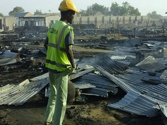 Residents of the Muna camp, near Maiduguri, gather near the site of an explosion on March 22, 2017. At least four suicide bomb blasts rocked a camp for migrants fleeing Boko Haram insurgents in restive northeastern Nigeria, killing at least three people and wounding 20, officials said. The blasts triggered …