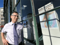In this Nov. 14, 2016 photo, Mayor Chris Louras poses outside an exhibit featuring Syrian art in downtown Rutland, Vt. After months of bitter debate, the down-on-its heels city is preparing to start accepting up to 100 Syrian refugees. Louras, the main proponent of bringing the refugees to his community, …