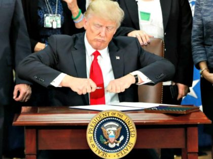 President Donald Trump takes the cap off a pen before signing executive order for immigration actions to build border wall during a visit to the Homeland Security Department in Washington, Wednesday, Jan. 25, 2017. (AP Photo/Pablo Martinez Monsivais)