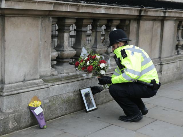 A police officer lays a floral tribute given by a member of the public beside a photo of PC Keith Palmer, the policeman who was stabbed to death as he guarded the Palace of Westminster from a terrorist in yesterday's attack on March 23, 2017 in London, England.