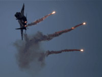 An Israeli Air Force fighter jet releases flares during an acrobatics display during a graduation ceremony in the Hatzerim air force base near the southern city of Beersheba, Israel, Thursday, Dec. 27, 2012. (AP Photo/Ariel Schalit)