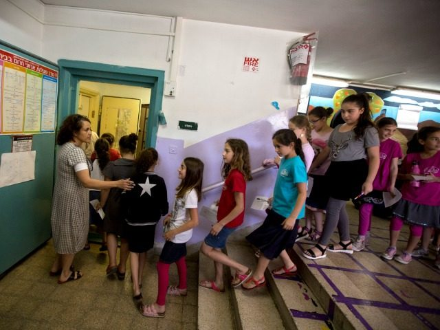 Israeli girls walk into a shelter as a siren is heard as part of an army drill simulating a rocket attack on Israel, in a school in Jerusalem, Tuesday, June 2, 2015. (AP Photo/Sebastian Scheiner)