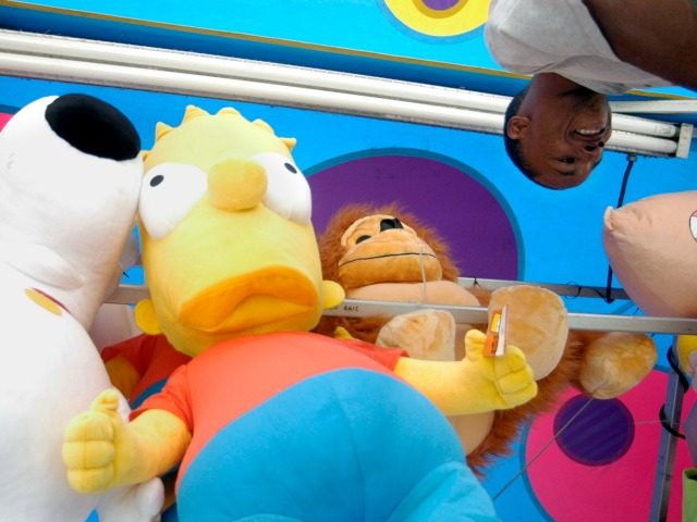Roger Broady, of Suffolk, Va, hangs stuff animals and cartoon characters on a carnival booth, Thursday, Sept. 6, 2005, on the Arkansas State Fairgrounds in preparation of the Arkansas State Fair. The fair is scheduled to open Friday and runs through Sunday Oct. 16. (AP Photo/Mike Wintroath)