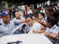 "Cuban security personnel detain a member of the Ladies in White dissident group during a protest on International Human Rights Day, Havana, December 10. Cuban police detained at least six protesters shouting ""Freedom"" and ""Long live human rights"" in Havana on Thursday and dissidents reported 100 arrests nationwide on U.N. …"