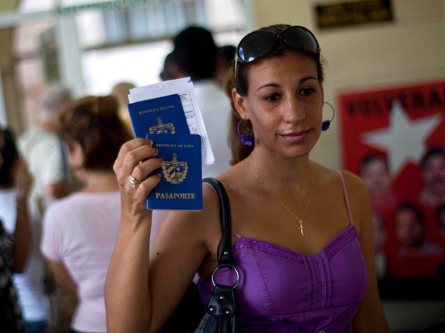 A woman shows her passport and that of her son to reporters as she leaves an immigration office in Havana, Cuba, Tuesday, Oct 16, 2012. The Cuban government announced Tuesday that it will no longer require islanders to apply for an exit visa, eliminating a much-loathed bureaucratic procedure that has been a major impediment for many seeking to travel overseas for more than a half-century. (AP Photo/Ramon Espinosa)