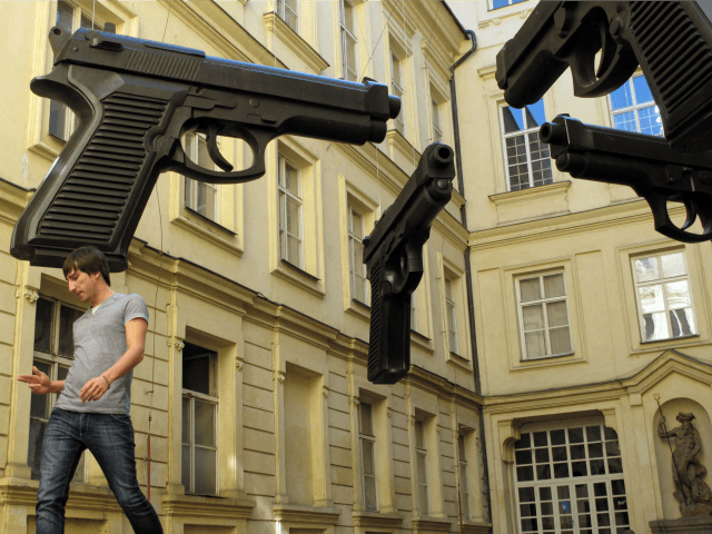 A young man makes a gesture in the shape of a gun while visiting an outdoor art exhibit at the Art Banka Museum of Young Art in Prague, Czech Republic, Thursday, Oct. 6, 2011. An art display by the artist Davida Cerneho, showing four replica guns, each over six feet …