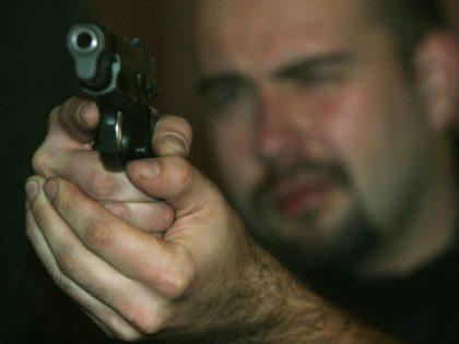 An unidentified sports shooter aims a Czech made CZ 9mm gun on a target at the shooting range in Prague, Czech Republic on Monday Nov. 17, 2003. (AP Photo/Petr David Josek)