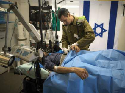 Israeli military medic tends a Syrian man who was wounded in the ongoing violence in Syria, in a military hospital located in the Golan Heights near the border with Syria on Tuesday, Feb. 18, 2014. Since the Syrian conflict erupted almost three years ago hundreds of Syrians have received treatment …