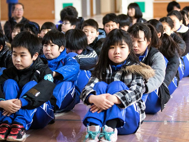 OGA, JAPAN - MARCH 17: Students at the Hokuyou Elementary School listen to instructions of the officials during a missile evacuation drill on Friday, March 17, 2017, in Kitaura, Oga, Akita Prefecture, Japan. During the drill, around 50 kids were instructed to walk slowly inside of a school gym, as if a missile had hit the the ground nearby. After a loud siren, people are instructed through a loudspeaker to move to safer ground in the school. People participated in the first missile evacuation drill organized by the Akita prefectural office and Oga city to prepare people in the event of a North Korean Missile strike on Japan. Recently, Three of four missiles fired by North Korea may have fallen into Japan's Exclusive Economic Zone and the Japanese government has lodged a strong protest against North Korea. (Photo by Richard Atrero de Guzman/Anadolu Agency/Getty Images)
