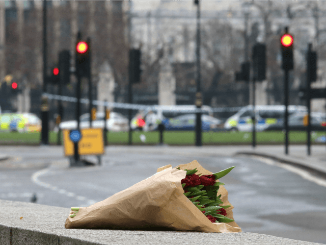 A floral tribute to the victims of yesterday's terror attack is left at the security cordon near Westminster Abbey in central London on March 23, 2017. Seven people have been arrested including in London and Birmingham over Wednesday's terror attack at the British parliament, the police said today, revising down …