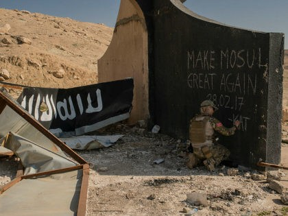 MOSUL, IRAQ - MARCH 9: A Norwegian volunteer medic writes 'Make Mosul Great Again' on the base of a destroyed Islamic State billboard in west Mosul, March 9, 2017. Iraqi forces are advancing into west Mosul, part of the offensive to retake the city some two years after it fell …