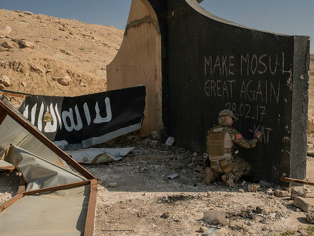 MOSUL, IRAQ - MARCH 9: A Norwegian volunteer medic writes 'Make Mosul Great Again' on the base of a destroyed Islamic State billboard in west Mosul, March 9, 2017. Iraqi forces are advancing into west Mosul, part of the offensive to retake the city some two years after it fell to Islamic State. (Photo by Martyn Aim/Getty Images)