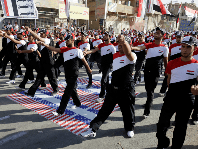 In this Thursday, May 26, 2011 file photo, militiamen loyal to cleric Muqtada al-Sadr march over the American flag while wearing shirts bearing the Iraqi flag in the Sadr City district of Baghdad, Iraq. Shiite militias backed by Iran have ramped up attacks on U.S. troops in Iraq, making June …
