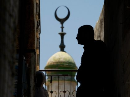 Backdropped by a mosque minaret Palestinians watch the funeral of Mohammed Al Amma, 17, in the West Bank village of Beit Ummar, near Hebron, Saturday, June 28, 2008. Al Amma was shot and killed by Israel troops during clashes in the village early Saturday morning, Palestinian medical sources said. (AP …