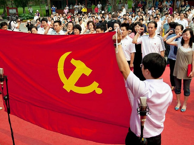 Participants at an event celebrating the 90th anniversary of the Chinese Communist Party salute the Communist Party flag in Beijing, China, on Tuesday, June 28, 2011. China's Communist Party celebrates its 90th anniversary on July 1. Photographer: Nelson Ching/Bloomberg via Getty Images