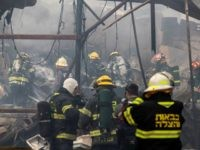 Israeli firefighters and rescue workers inspect the rubble after a fire ripped through a fireworks warehouse on March 14, 2017, in the village of Porat near Netanya. Police said two bodies were recovered from the warehouse and an investigation into the fire was continuing. / AFP PHOTO / JACK GUEZ …