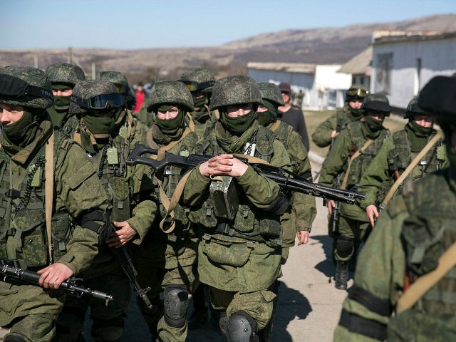 Military personnel, believed to be Russian servicemen, walk outside the territory of a Ukrainian military unit in the village of Perevalnoye outside Simferopol March 3, 2014. REUTERS/Baz Ratner