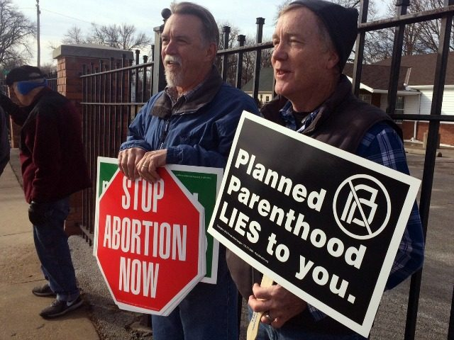 Marvin Naegele, 62, of Walnut, Iowa, left, and Lon Schroeder, 61, of Council Bluffs hold protest signs during a protest on Saturday, Feb. 11, 2017 in Council Bluffs, Iowa. Rallies aimed at urging Congress and President Donald Trump to end federal funding for Planned Parenthood are scheduled across the country. (AP Photo/Margery Beck)