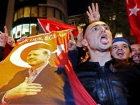 Demonstrators with banners of Turkish President Recep Tayyip Erdogan gather outsidethe Turkish consulate to welcome the Turkish Family Minister Fatma Betul Sayan Kaya, who decided to travel to Rotterdam by land after Turkish Foreign Minister Mevlut Cavusoglu's flight was barred from landing by the Dutch government, in Rotterdam, Netherlands March …