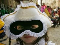 Avital Politi, 4, dressed as a princess from Venice, looks out from her mask during the Jewish festival of Purim March 15,2006 in Jerusalem, Israel. Acting Prime Minister Ehud Olmert has committed himself to pull out of most of the West Bank should his Kadima party win the upcoming March …