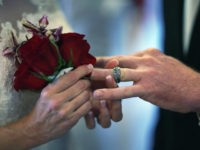 WEST PALM BEACH, FL - FEBRUARY 14: Luanne Round slips a ring on the finger of her husband, Matthew Round as they are wed during a group Valentine's day wedding at the National Croquet Center on February 14, 2013 in West Palm Beach, Florida. The group wedding ceremony is put …