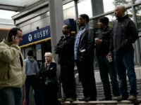 People stand on a street bench next to Husby subway station as they attend a demonstration against police violence and vandalism in the Stockholm suburb of Husby on May 22, 2013. Rioting spread across Stockholm immigrant districts in a third night of unrest, raising fears that decades of integration efforts …