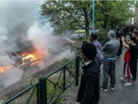 Bystanders take photos of a row of burning cars in the Stockholm suburb of Rinkeby after youths rioted in several different suburbs around Stockholm, Sweden for a fourth consecutive night on May 23, 2013. In the suburb of Husby, where the riots began on Sunday in response to the fatal …