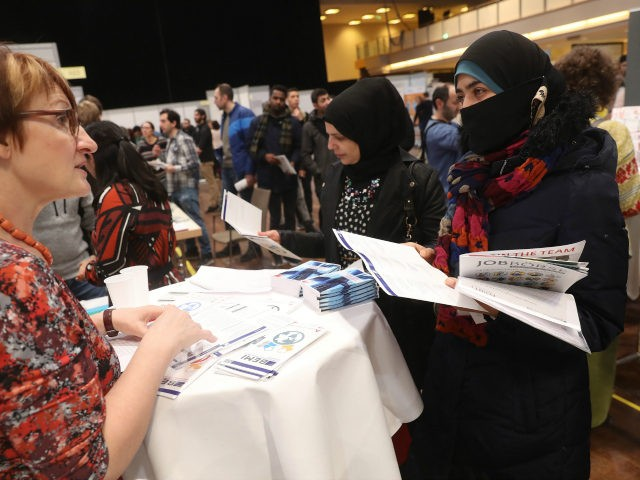 BERLIN, GERMANY - JANUARY 25: Two women from Jordan (C) and Syria learn about job opportunities at a stand at the second annual jobs fair for refugees and migrants at the Estrel hotel and conference venue on January 25, 2017 in Berlin, Germany. The intiative brings together exhibitors from retail, …