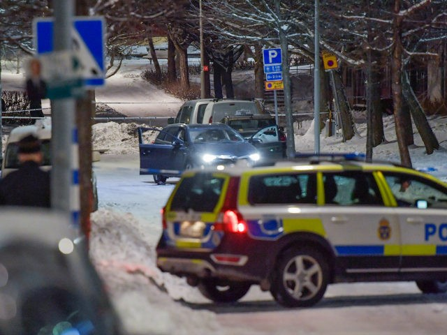 A shot-up car stands behind police cordons, where two men were found with gunshot wounds in Kista, Northwestern Stockholm, on late March 8, 2017. Both men were later pronounced dead at the hospital. / AFP PHOTO / TT News Agency / Jessica GOW / Sweden OUT (Photo credit should read …