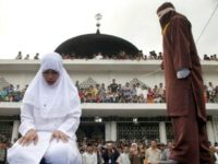 An officer canes a woman who violated strict Syariah laws